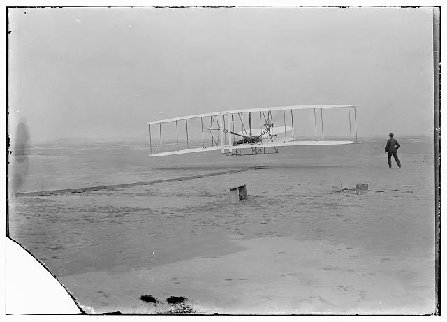 The first powered, controlled, sustained flight. Orville Wright is at the controls while Wilbur runs alongside. Photo from Library of Congress